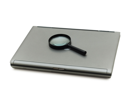 Magnifying Glass atop Laptop Computer