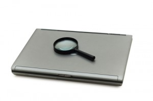 Laptop and Magnifying Glass