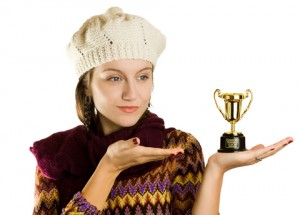 Woman in hat with tiny trophy