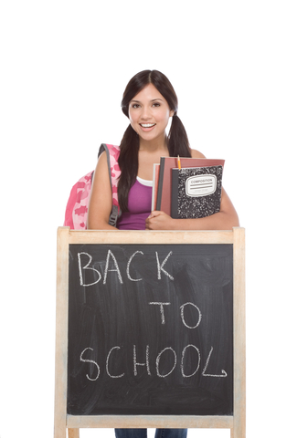"Girl holding books and backpack in front of a chalkboard that reads ""Back to School."""