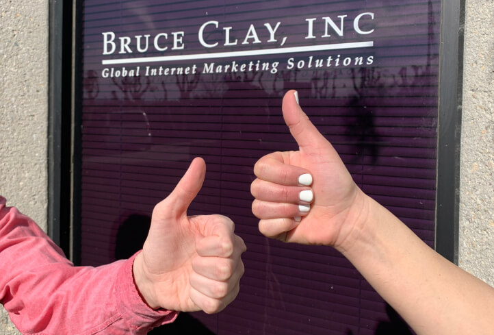 Thumbs up in front of Bruce Clay brand sign.