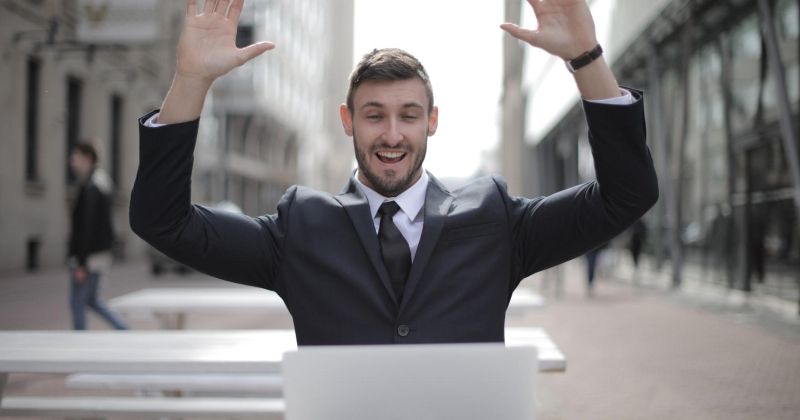 Man in suit looking at laptop with hands up, winning at SEO.