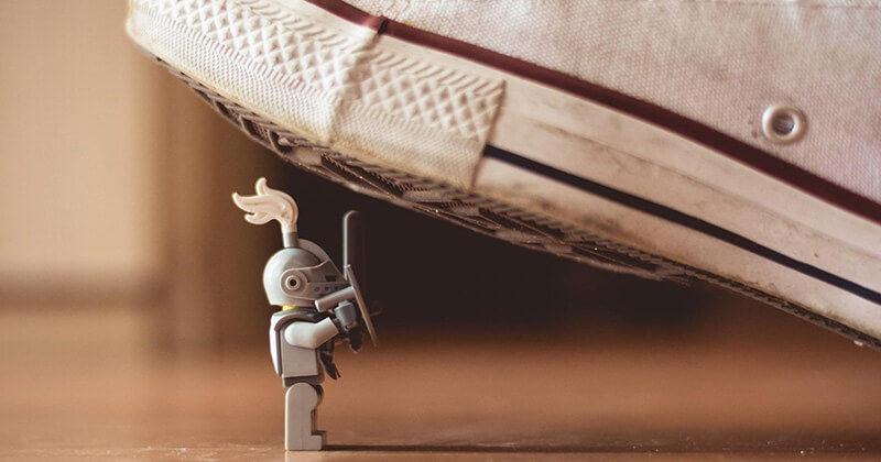 A small toy knight battles a giant shoe in a David versus Goliath scenario.